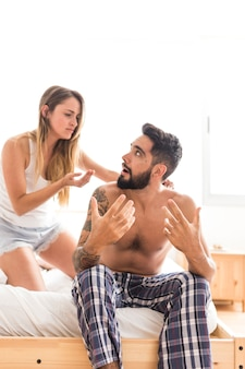 Молодая пара спорить на кровати в спальне