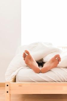 毛布の下の人の足