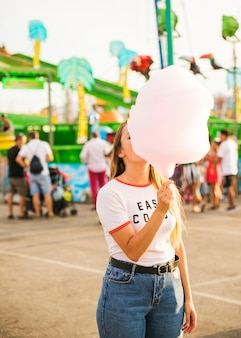 ピンクのキャンディーフロスを食べている女性