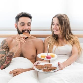朝の朝食を取るベッドに座っているカップル