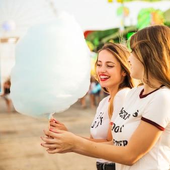 Две счастливые друзья-женщины с конфеткой