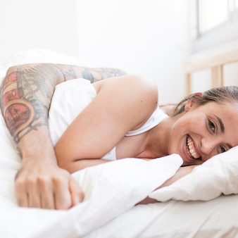 彼女の夫と一緒に寝る笑顔の若い女性