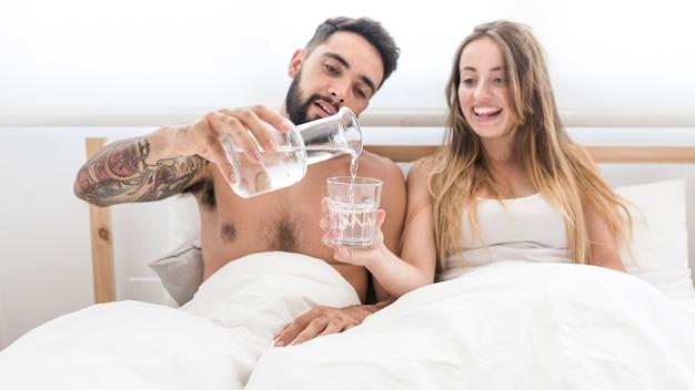 寝室に彼女の妻のためにガラスに水を注ぐ男