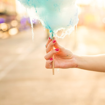 青いキャンディーフロスを保持している女性の手のクローズアップ