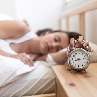 Женщина, спать на кровати, выключая будильник