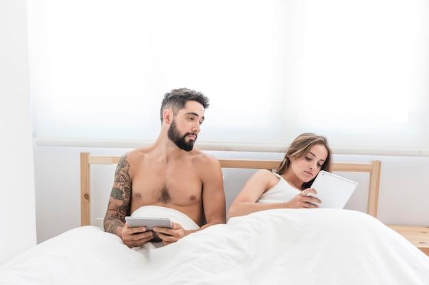 Человек, глядя на свою жену, используя цифровую таблетку на кровати