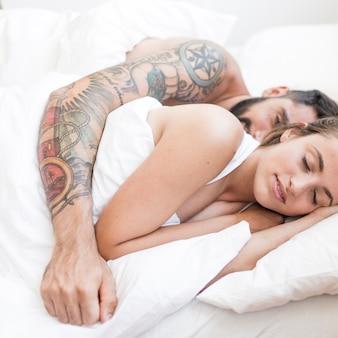ベッドに一緒に横たわっている若いカップル