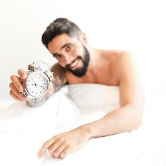 目覚まし時計を示すベッドに座っている笑顔の若い男