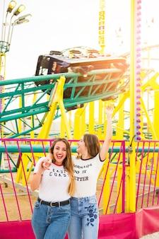 ジェットコースターの前で一緒に遊んでいる幸せな女性の友達
