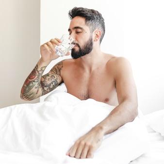 Человек, сидящий на кровати, выпивая стакан воды