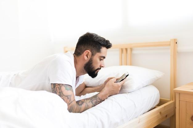 携帯電話を使ってベッドに横たわっている男