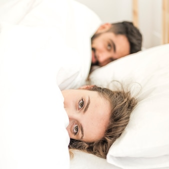 ベッドに横たわっている毛布で覆われたカップル