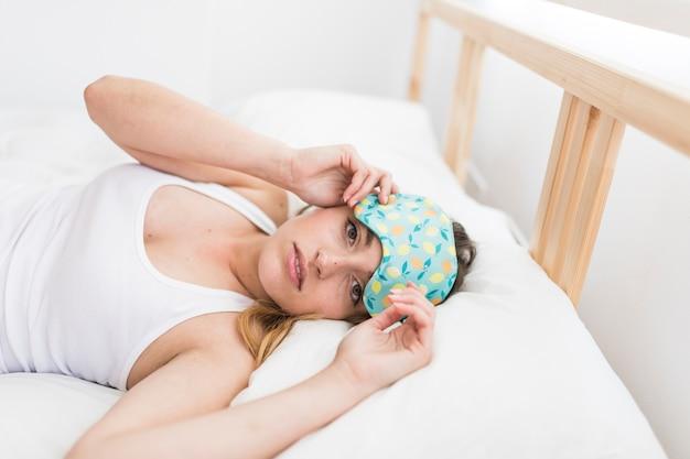 Молодая женщина, лежа на кровати с глазной маской