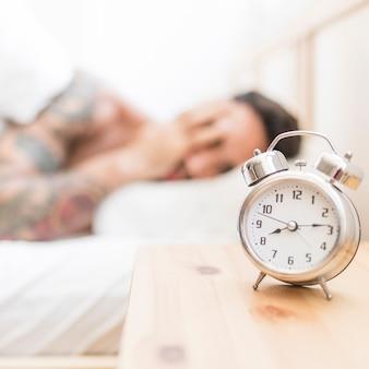 木製の机の上に目覚まし時計で眠っている男