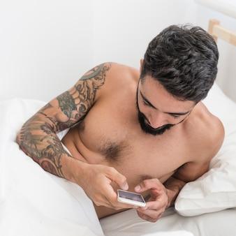 ベッドで携帯電話を使用している若い男