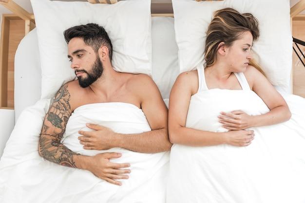ベッドに横たわっている悲しい夫婦の高い角度の光景