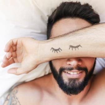 ベッドの上で寝る男の手の上に描かれたまつ毛