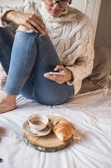 コーヒーとクロワと毛布に座っている若い女性