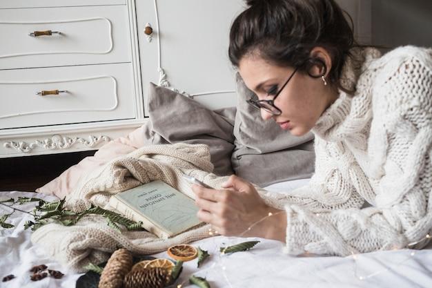 Молодая женщина, лежа на одеяло и с помощью смартфона