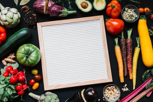 黒い背景にカラフルな野菜と木製の白いフレームのオーバーヘッドビュー