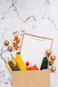大理石の背景に茶色の紙袋から落ちるクリップボードに野菜や紙