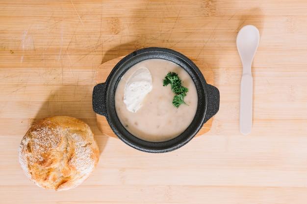 木製のテクスチャの背景にパンとスプーンできのこクリームスープ