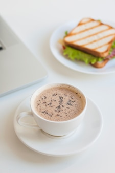 白い背景にサンドイッチとコーヒーの白いカップ