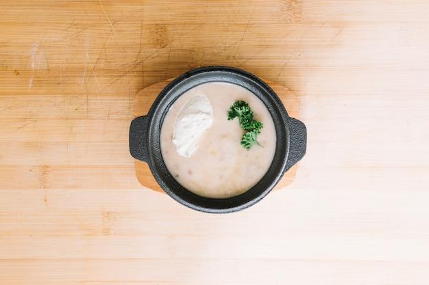 木製の背景の上にコンテナのおいしいキノコのクリームスープ