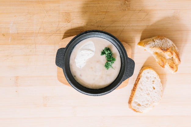 木製のテクスチャの背景にパンスライスとキノコのスープ