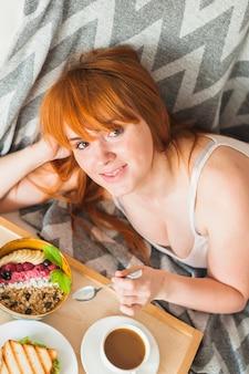 コーヒーで朝食にオートミールとサンドイッチを楽しむ笑顔の若い女性のオーバーヘッド