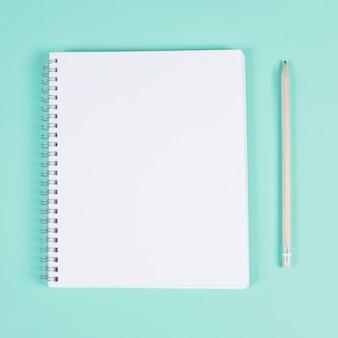 ターコイズ色の背景に鉛筆で空白のスパイラルノート