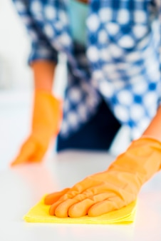 黄色の手袋を着て女性の手のクローズアップは、黄色のナプキンで白い表面を拭く