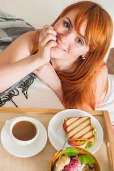 木製の皿で朝食付きの若い女性の頭上の眺め