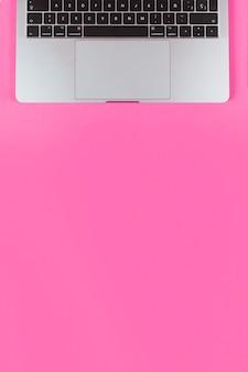 テキストのコピースペースとピンクの背景を介して開いたラップトップ