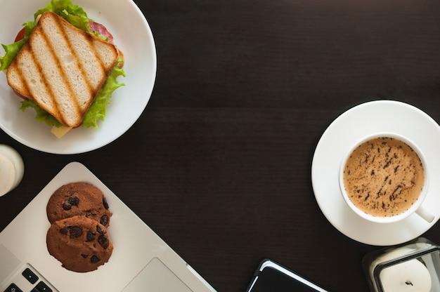 焼かれたクッキー;サンドイッチ;黒の背景にコーヒーカップ