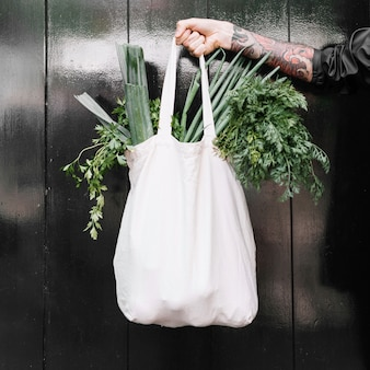 白い食料品の袋を保持している男の手のクローズアップは、葉の野菜でいっぱい