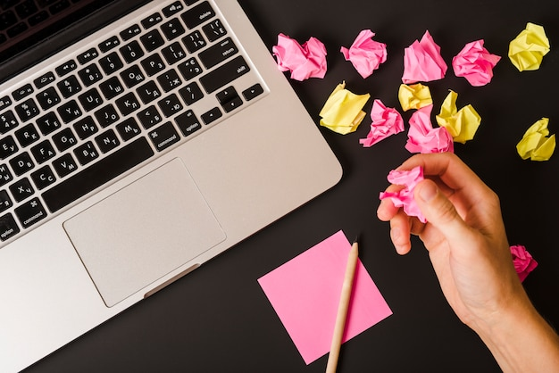 Рука человека с мятой бумагой с ноутбуком; ручка и клейкая бумага на черном фоне