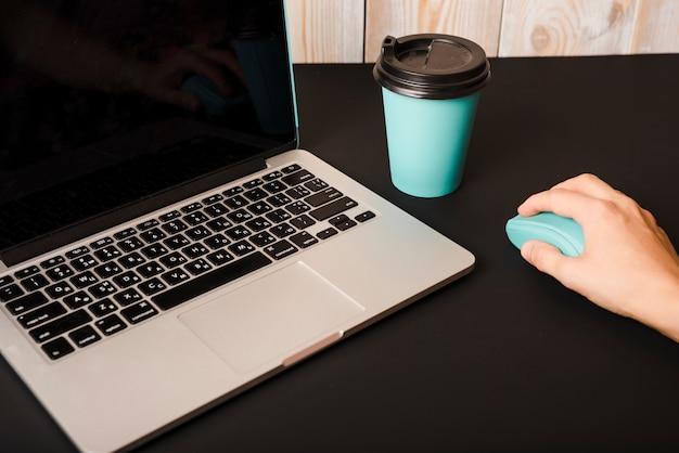 黒い机の上にテイクアウトコーヒーカップとラップトップを持つマウスを使用して手