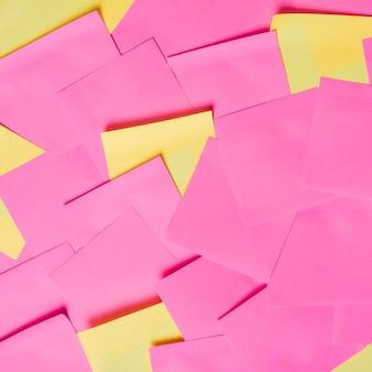 黄色とピンクの空白の接着剤のメモ帳のフルフレーム