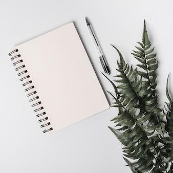 スパイラルメモ帳。ペンと緑の偽のシダの葉は、白い背景に