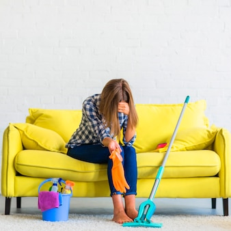 Разочарованная молодая женщина, сидя на диване с чистящим оборудованием