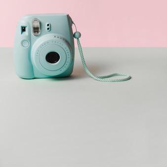 ピンクの背景にグレーの机の上にミニブルーインスタントカメラ