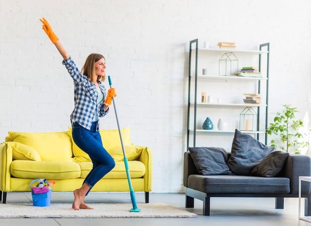Улыбается молодая женщина, танцы в гостиной с чистящим оборудованием