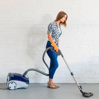 Вид сбоку молодой женщины-уборщика с пылесосом перед кирпичной стеной