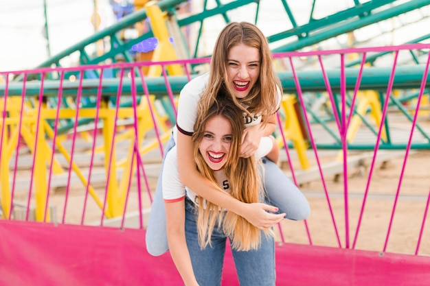 遊園地の幸せな若い友人たち