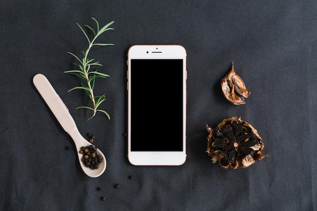 ローズマリーに囲まれたスマートフォン。ブラックペッパー、ニンニク、暗い背景