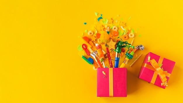 黄色の表面にキャンデーやパーティーアクセサリーと開いているギフトボックスの高い角度のビュー