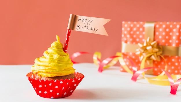 贈り物とリボンの近くの幸せな誕生日の旗とカップケーキのクローズアップ
