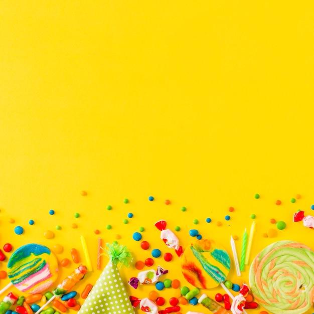 黄色の背景の下にある様々なキャンディーやパーティーの帽子