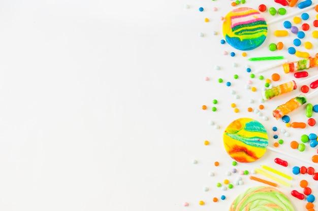 白い表面上の様々なカラフルなキャンデーの高い角度のビュー